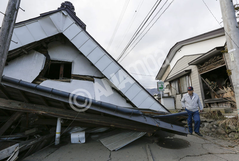 epa04500468 A resident walks next to a collapsed house damaged in a 6.7-magnitude earthquake in the ski resort village of Hakuba, central Japan, 23 November 2014. At least 57 people were injured in a magnitude-6.7 earthquake that struck central Japan overnight, authorities said.  EPA/KIMIMASA MAYAMA