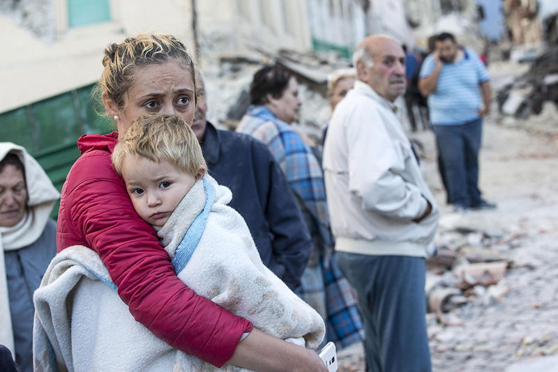epaselect epa05508216 A mother embraces her son in Amatrice, central Italy, central Italy, 24 August 2016, following a 6.2 magnitude earthquake, according to the United States Geological Survey (USGS), that struck at around 3:30 am local time (1:30 am GMT). The quake was felt across a broad section of central Italy, including the capital Rome where people in homes in the historic center felt a long swaying followed by aftershocks. According to reports at least 21 people died in the quake, 11 in Lazio and 10 in Marche regions.  EPA/MASSIMO PERCOSSI