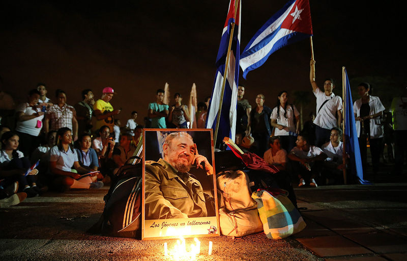 A portrait of Fidel Castro is pictured against dozens of people (background) participating in a vigil commemorating the late Cuban leader in Camaguey, Cuba, early 02 December 2016. Former Cuban President Fidel Castro died at the age of 90, in Cuba, on 25 November 2016. Banner reading 'The young will not fail.'  EPA/ALEJANDRO ERNESTO