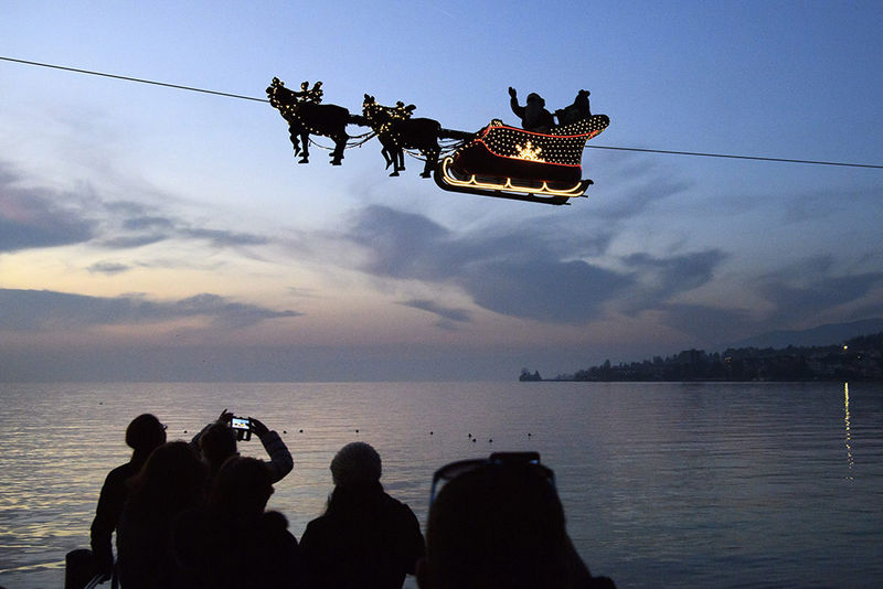 epaselect epa05662603 Santa Claus waves to the crowd from a flying sleigh drawn by reindeer on a cable suspended over Lake Geneva in front of the Swiss and French alps, on the first day of the 22nd Christmas Markets in Montreux, Switzerland, on Tuesday, December 6, 2016. The cable is suspended 385 meters above the lake.  EPA/LAURENT GILLIERON