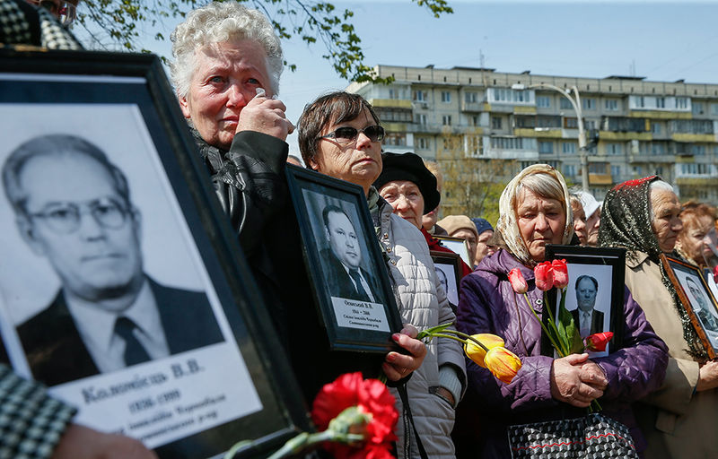 Women react as they hold portraits of their lost husbands near a monument honoring people who were killed in cleanup efforts after the Chernobyl nuclear power plant disaster, during a memorial ceremony in Kiev, Ukraine, 26 April 2017. In the early hours of 26 April 1986 the Unit 4 reactor at the Chernobyl power station blew apart. Facing nuclear disaster on unprecedented scale Soviet authorities tried to contain the situation by sending thousands of ill-equipped men into a radioactive maelstrom. The men barely lasted more than a few weeks suffering lingering painful deaths. The explosion of Unit 4 of the Chernobyl nuclear power plant is still regarded as the biggest accident in the history of nuclear power generation. Ukrainians mark the 31th anniversary of Chernobyl's tragedy on 26 April 2017.  EPA/SERGEY DOLZHENKO