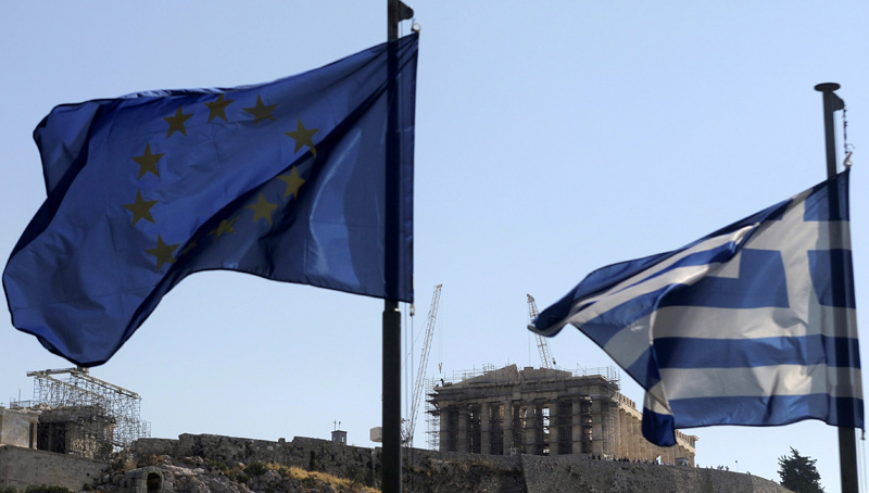epa04834769 A Greek and a European Union flag flutter in front of the Acropolis hill in Athens, Greece, 07 July 2015. Eurozone member states on 07 July are waiting for the Greek proposals in order to discuss a new aid programme for Greece. Prime Minister Alexis Tsipras is heading to Brussels to participate in the summit. In the eurozone summit, that will also be attended by ECB president Mario Draghi and Eurogroup chief Jeroen Dijsselbloem, officials will discuss the actions to be taken after the referendum.  EPA/ORESTIS PANAGIOTOU